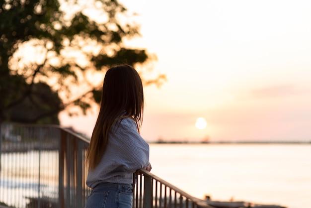 Zijaanzichtvrouw die de zonsondergang bekijkt