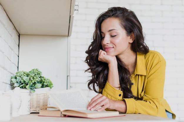 Zijaanzichtvrouw die een boek leest