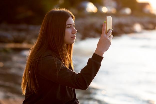 Zijaanzichtvrouw die een foto van de zee neemt