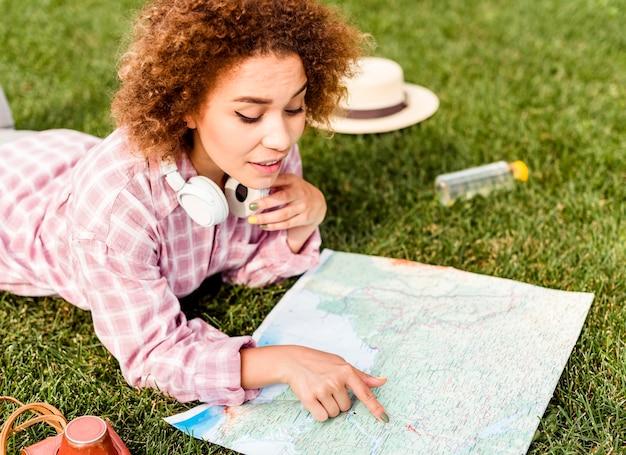 Zijaanzichtvrouw die een kaart voor haar nieuwe bestemming controleert