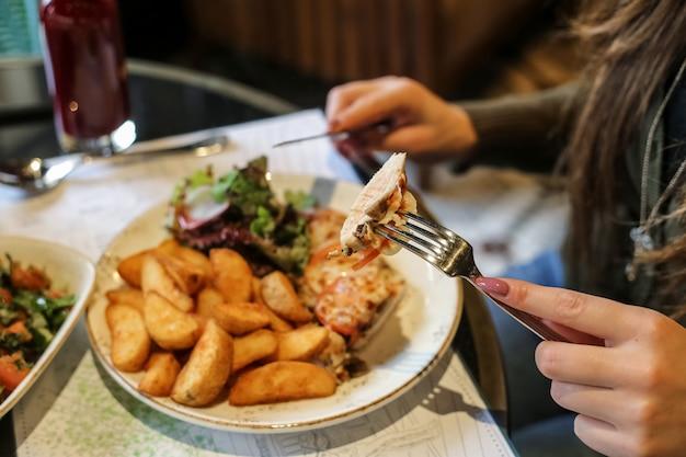 Zijaanzichtvrouw die gebraden kip met aardappels eten