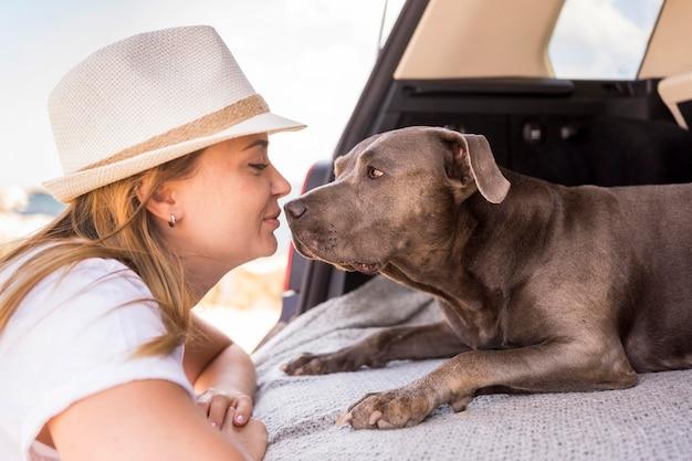 Zijaanzichtvrouw die haar hond bekijkt