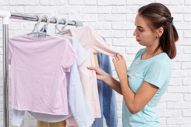 Zijaanzichtvrouw die haar kleren bekijkt