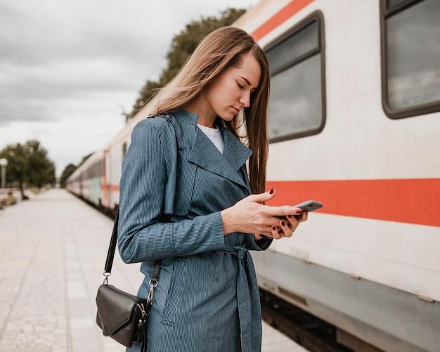 Zijaanzichtvrouw die haar mobiele telefoon bekijkt