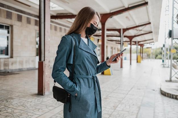 Zijaanzichtvrouw die haar mobiele telefoon controleert
