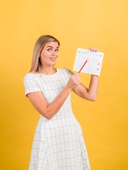 Zijaanzichtvrouw die haar periodekalender toont