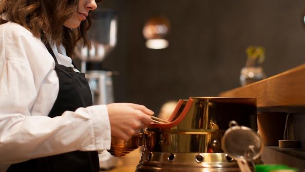 Zijaanzichtvrouw die in koffiewinkel werkt
