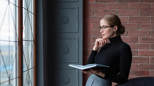 Zijaanzichtvrouw die met boek op venster kijken
