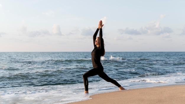 Zijaanzichtvrouw die met exemplaarruimte mediteren