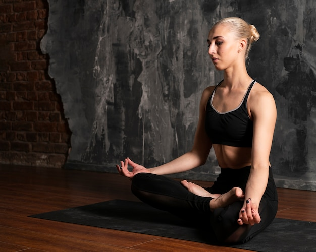 Zijaanzichtvrouw die met gipspleisterachtergrond mediteren