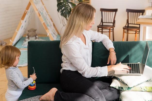 Zijaanzichtvrouw die met laptop werkt