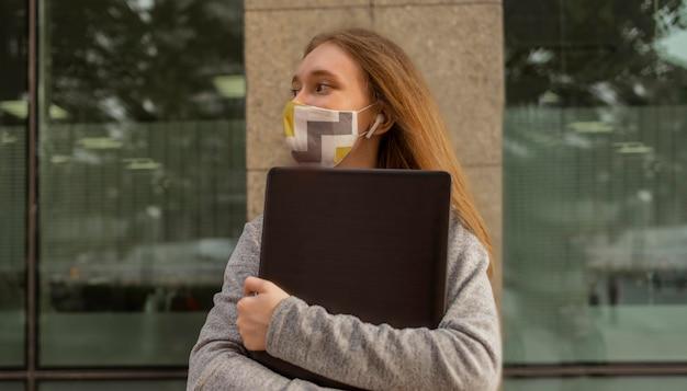 Zijaanzichtvrouw die met medisch masker haar laptop buiten houdt
