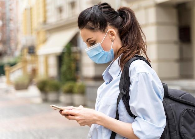 Zijaanzichtvrouw die met medisch masker haar telefoon controleert