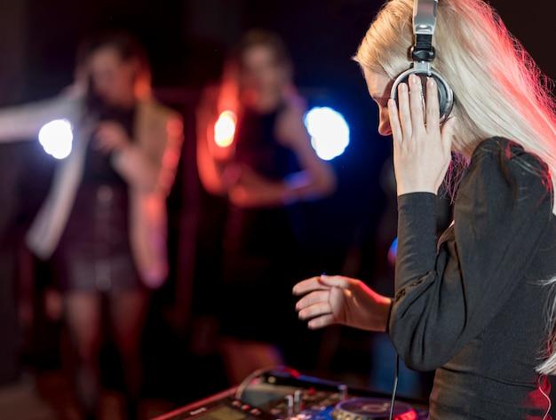 Zijaanzichtvrouw die muziek mengen