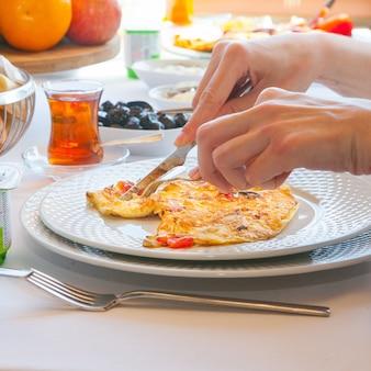 Zijaanzichtvrouw die omelet in keuken met thee, olijven, vruchten op achtergrond eten.