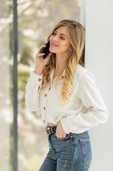 Zijaanzichtvrouw die op de telefoon spreekt
