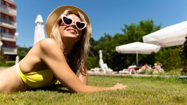 Zijaanzichtvrouw die op gras legt