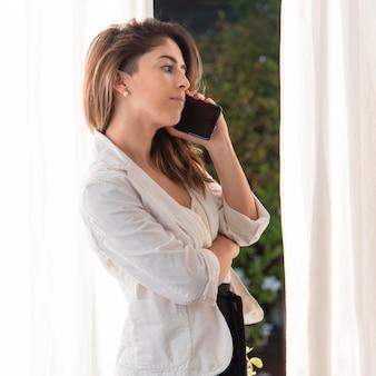 Zijaanzichtvrouw die op telefoon spreekt