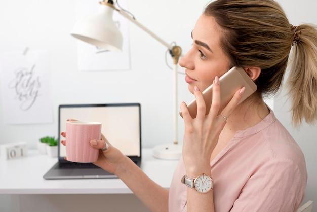 Zijaanzichtvrouw die over telefoon spreken