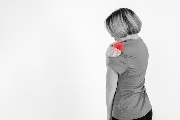 Zijaanzichtvrouw die pijnlijke schouder masseert
