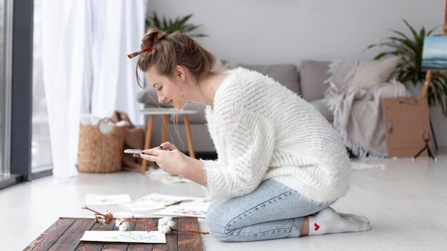 Zijaanzichtvrouw die thuis een vlog maakt van haar schilderijen