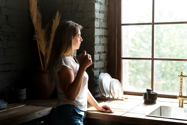 Zijaanzichtvrouw die uit het venster kijkt