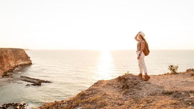 Zijaanzichtvrouw die van de zonsondergang met exemplaarruimte genieten