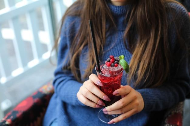 Zijaanzichtvrouw die verfrissende cocktail met bessen en stro drinken