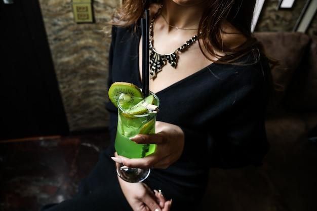 Zijaanzichtvrouw die verfrissende cocktail van kiwi drinken