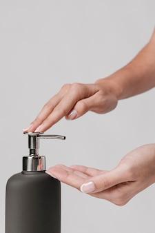 Zijaanzichtvrouw die vloeibare zeep gebruikt
