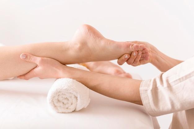 Zijaanzichtvrouw die voet masseren
