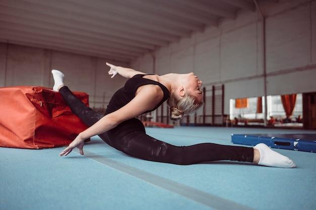 Zijaanzichtvrouw die voor gymnastiekolympische spelen uitoefent