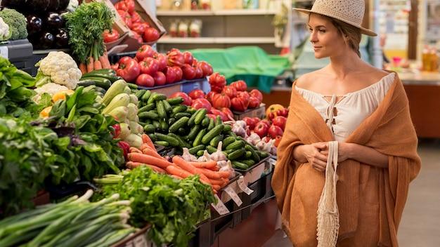 Zijaanzichtvrouw die zonnehoed draagt die groenten bekijkt