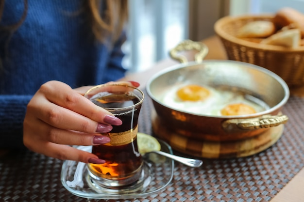 Zijaanzichtvrouw het drinken thee met gebraden eieren in een pan met brood in een mand