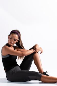 Zijaanzichtvrouw in de zitting van het gymnastiekkostuum
