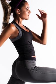 Zijaanzichtvrouw in gymnastiekkostuum het uitoefenen