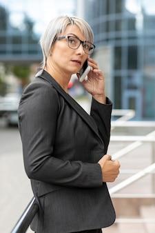 Zijaanzichtvrouw in kostuum die over telefoon spreken