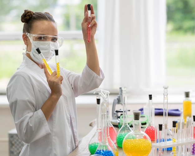 Zijaanzichtvrouw in laboratorium die experimenten doen