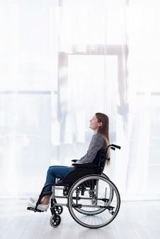 Zijaanzichtvrouw in rolstoel