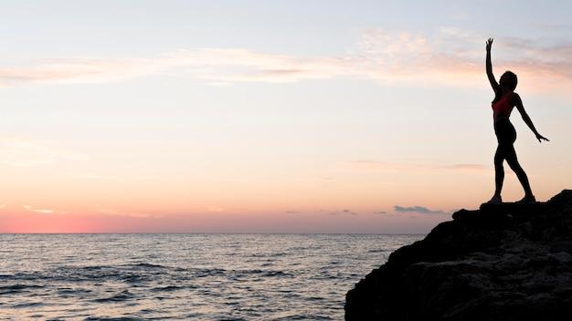Zijaanzichtvrouw in sportkleding die zich op een kust met exemplaarruimte bevindt