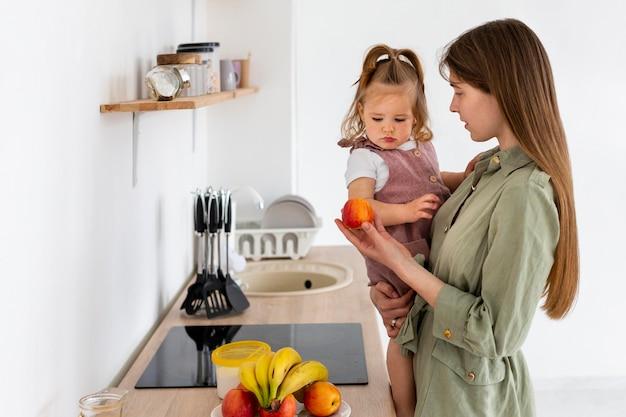 Zijaanzichtvrouw met jong geitje in keuken