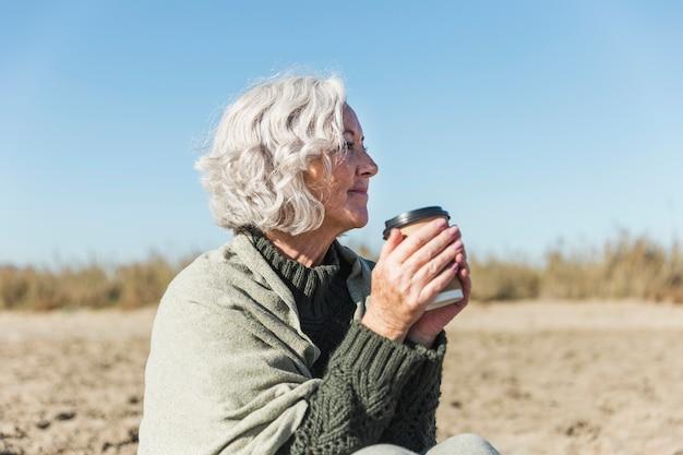 Zijaanzichtvrouw met koffie in openlucht