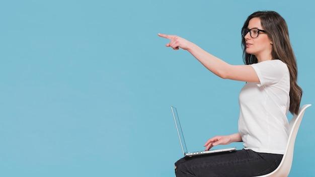 Zijaanzichtvrouw met laptop exemplaarruimte