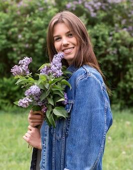 Zijaanzichtvrouw met lila bloemen