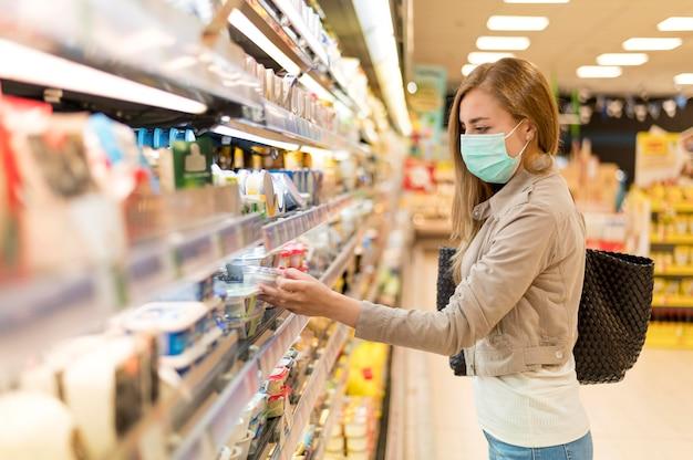 Zijaanzichtvrouw met masker bij kruidenierswinkel het winkelen