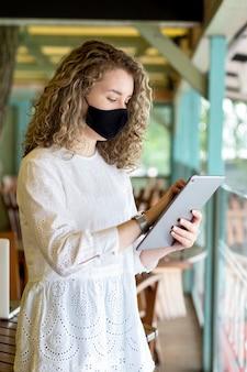 Zijaanzichtvrouw met masker die tablet gebruiken