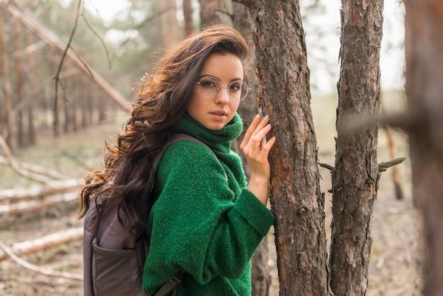 Zijaanzichtvrouw naast bomen