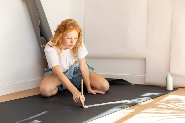 Zijaanzichtvrouw op vloer het schilderen