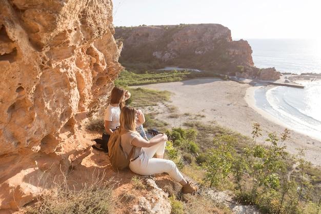 Zijaanzichtvrouwen die op een kust met exemplaarruimte zitten