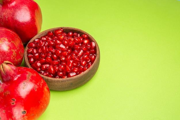 Zijaanzichtvruchten de smakelijke zaden van granaatappel in de kom drie rijpe rode granaatappels